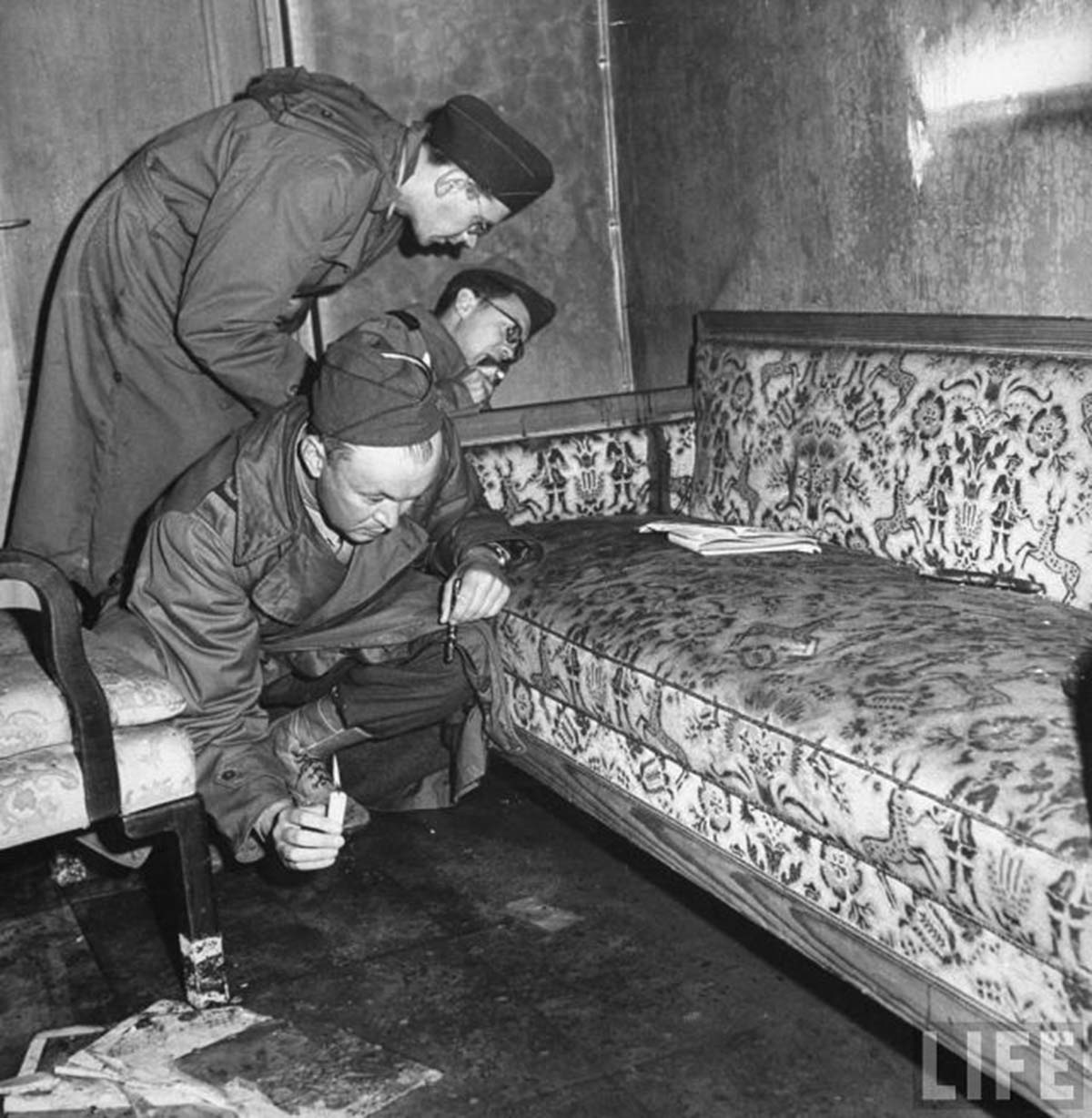 American soldiers inspect the couch where Adolf Hitler and Frau Hitler committed suicide. The soldier in the foreground appears to be looking at the bloodstains on the carpet. It would have been quite dark in there (without the photographer's flash) if all they had was candles. It would not surprising if this was some kind of