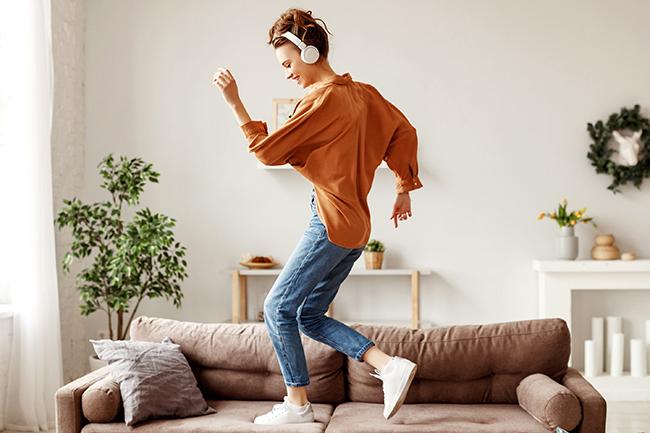 Moça dançando com headphones no sofá