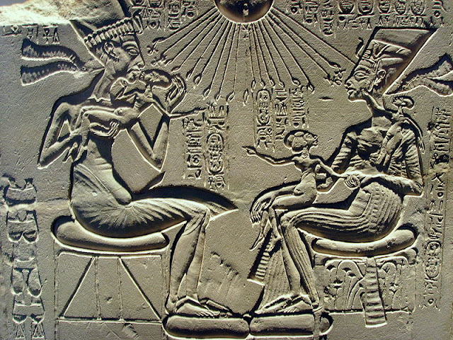 "Akhenaten, Nefertiti and their children receiving the ""breath of life"" from the rays of Aten, some of which terminate in hands holding ankhs."