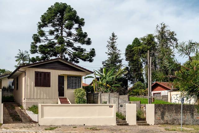 A casa de madeira com pinheiro ao fundo