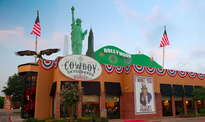 "a building called the ""Cowboy Skyscraper Buffet."" There's American flag bunting around the roof, two American flags, an eagle, the Washington monument, the Statue of Liberty, the Empire State Building, and the Hollywood hills on top. There's a sign with Uncle Sam pointing at you with a stern face saying ""I WANT YOU TO STUFF YOURSELF"""
