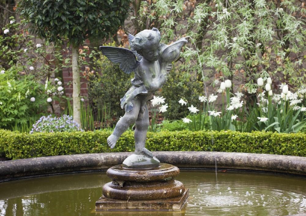 Estanque y fuente con escultura en romántico jardín inglés