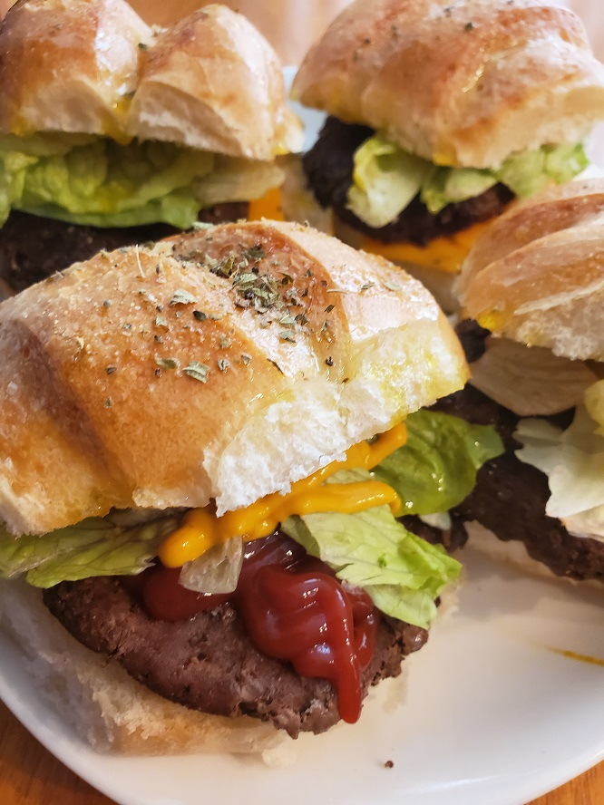 these are Italian hamburgers dressed with lettuce tomatoes and in hard rolls