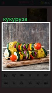 лежат несколько шампуров с кукурузой и другими овощами