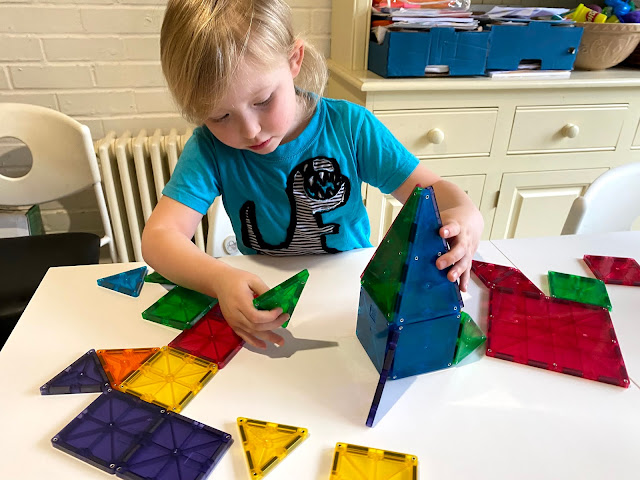 A 5 year old working out which way to attach a triangle to a rocket