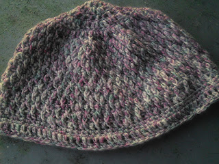 A textured crochet hat laying flat.  The hat is made in a pastel variegate red/white/purple yarn.