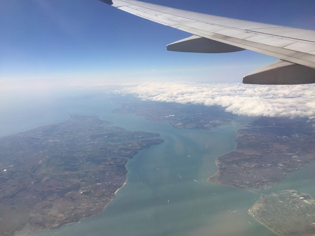 View out of an aeroplane window towards islands and sea and blue sky