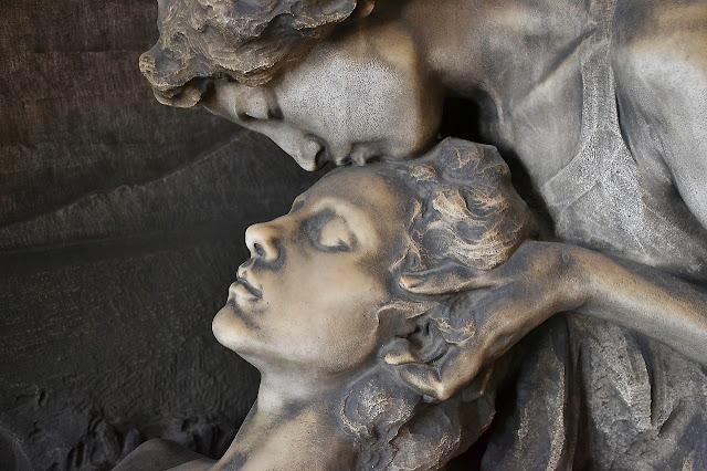 Eine Skulptur: Eine Frau beugt sich über die andere, küsst sie auf die Stirn, massiert ihren Kopf.