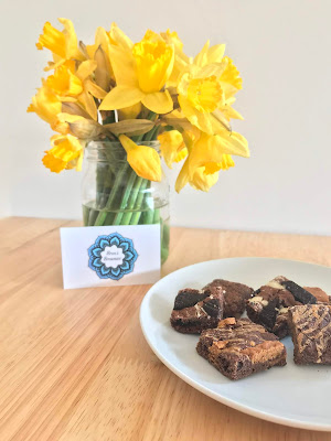 a plate of vegan brownies next to a jug of daffodils