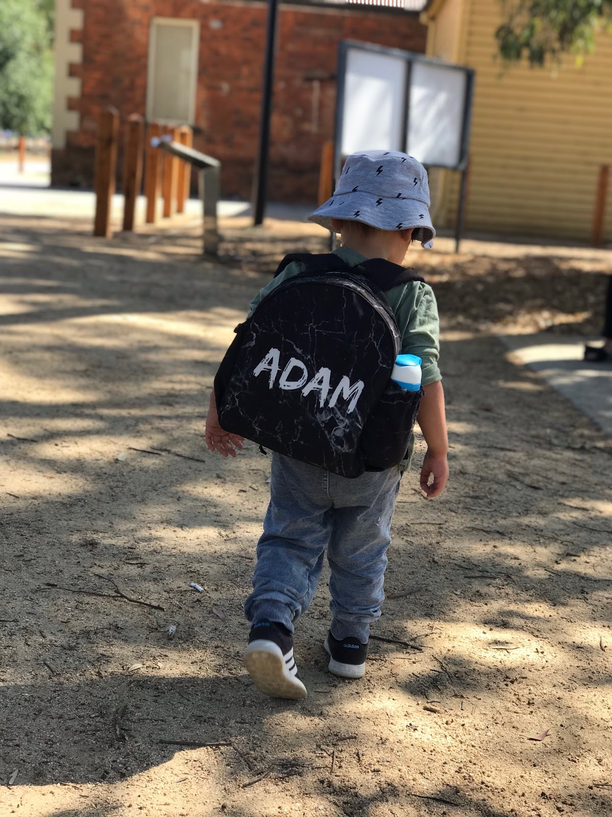 Image is a photo of a toddler walking away from the camera outdoors. He is wearing a backpack with black marble print and white text spelling ADAM. He is also wearing a grey wide brim hat and a long sleeve green top, with blue jeans and black sneakers. In the background, a building with red brick is visible.
