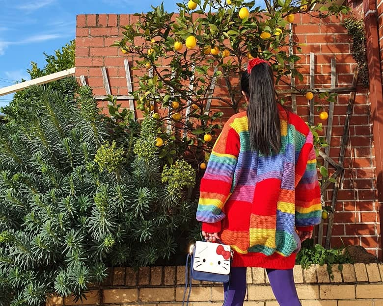 a picture of a girl wearing a crocheted rainbow jumper, holding a Hello Kitty handbag, with plants on the background