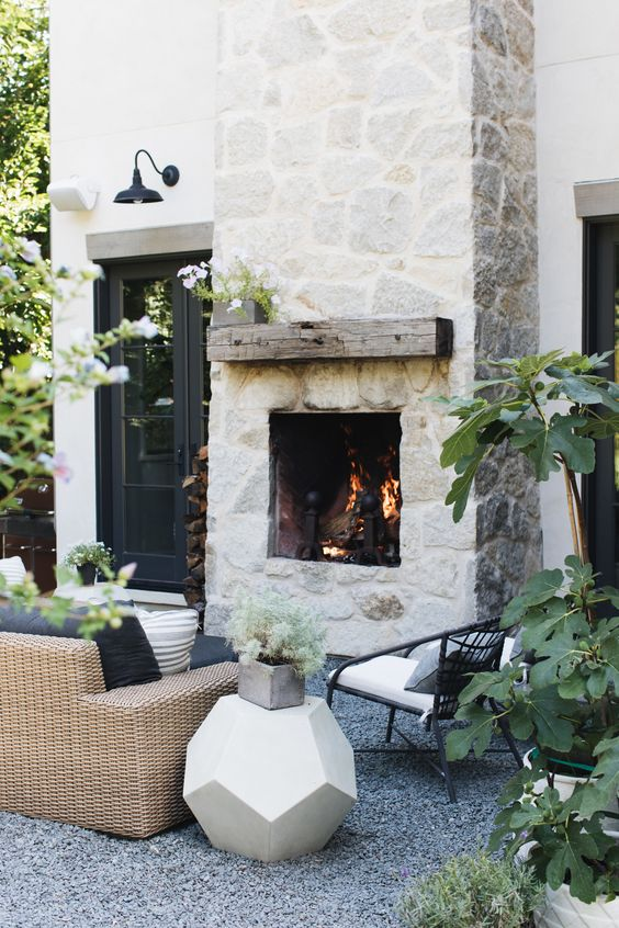 Outdoor sitting area with fireplace and barn light above door