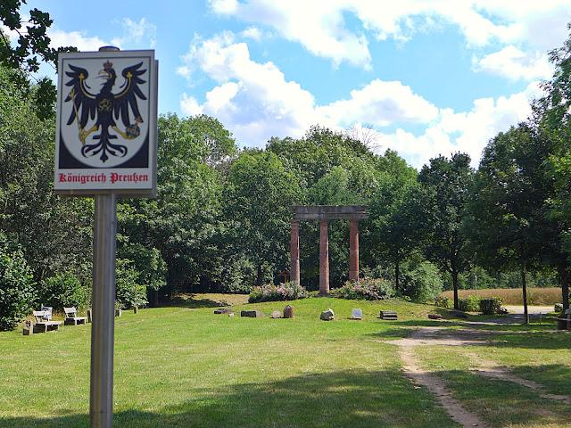 Wald mit Wiese, wo Bänke, alte Grenzsteine eine Ruine zu sehen sind