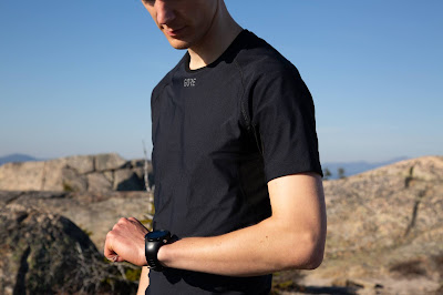 A young man wearing a black GORE WINDSTOPPER short sleeve t-shirt, center of frame, looks down at his running watch while standing amidst boulders with mountains seen far off in the distance.