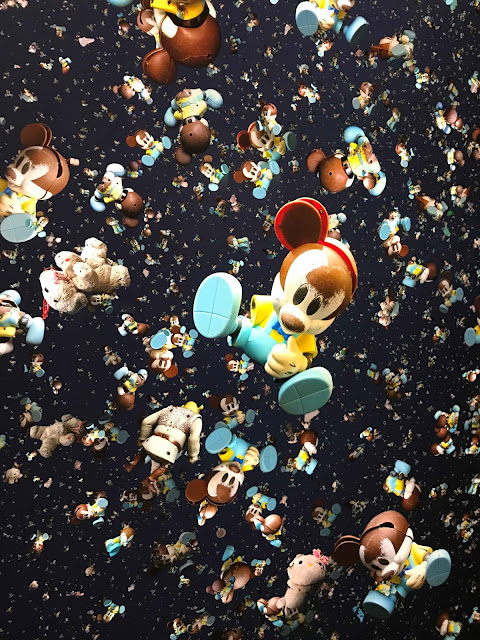 Hundreds of colourfull broken plastic dolls in front of black canvas.