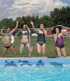 Four female campers jumping into crystal blue pool at Camp Kupugani, Chicago.