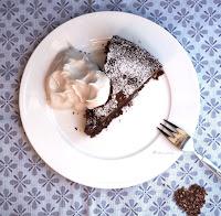 Ein Stück veganer Schokonuss Kuchen mit Kirschen und veganer Sahne