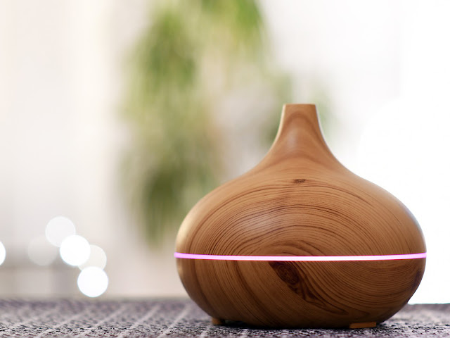 Wooden essential oils diffuser with a pink light accent