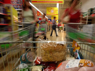 In the foreground there is a view of the Thanksgiving goodies inside a shopping cart, in the background is a blurred out view of a grocery store aisle.