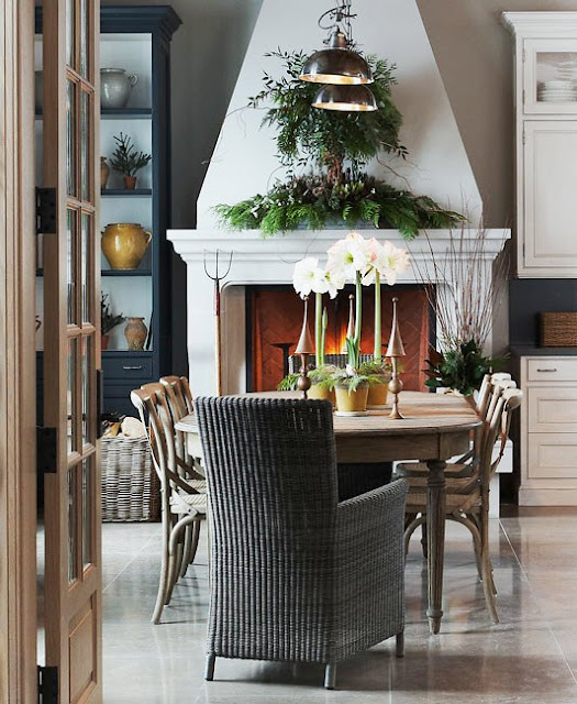 michael graydon's rustic dining room with wicker host chair and green holiday garland over a large white fireplace