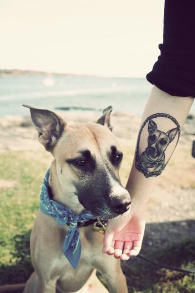 Foto de una chica con su perro, ella luce Precioso tatuaje de un perro