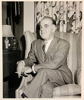A photograph of an older Flanigan sitting in a chair looking bemused