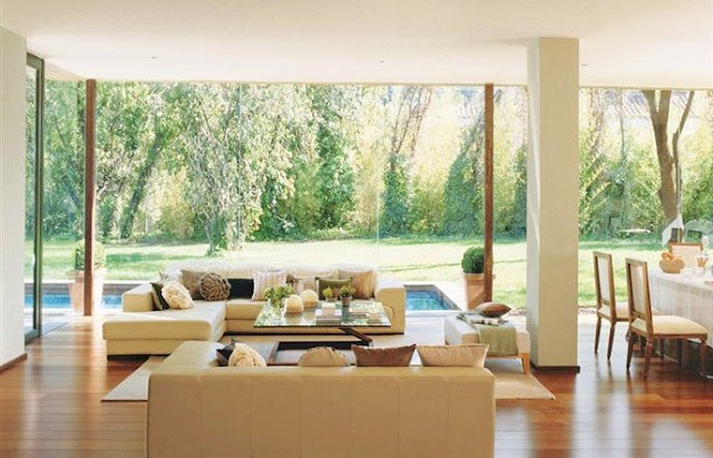 Living room with glass walls, wood floor and dueling sofas in Spain