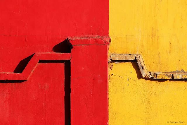 A Minimalist Photograph of a Wall with two primary colors, red and yellow.