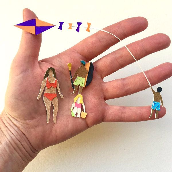 miniature cut paper figures dressed for a day at the beach