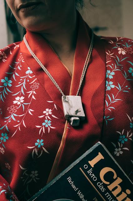Mulher com colar de cerâmica e livro do i-ching nas mãos