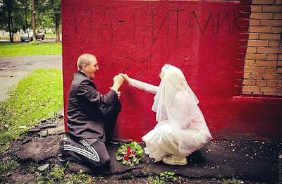 Brautpaar zeichnet Herz mit Pfeil an Wand lustig