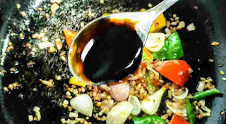 Pouring soya sauce with red chilli sauce, vinegar and vegetables for chilli chicken