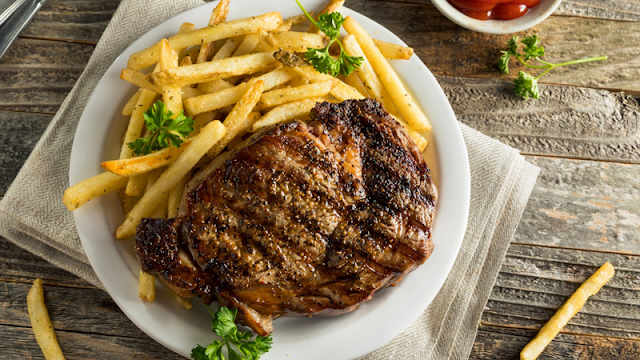a large steak served with french fries