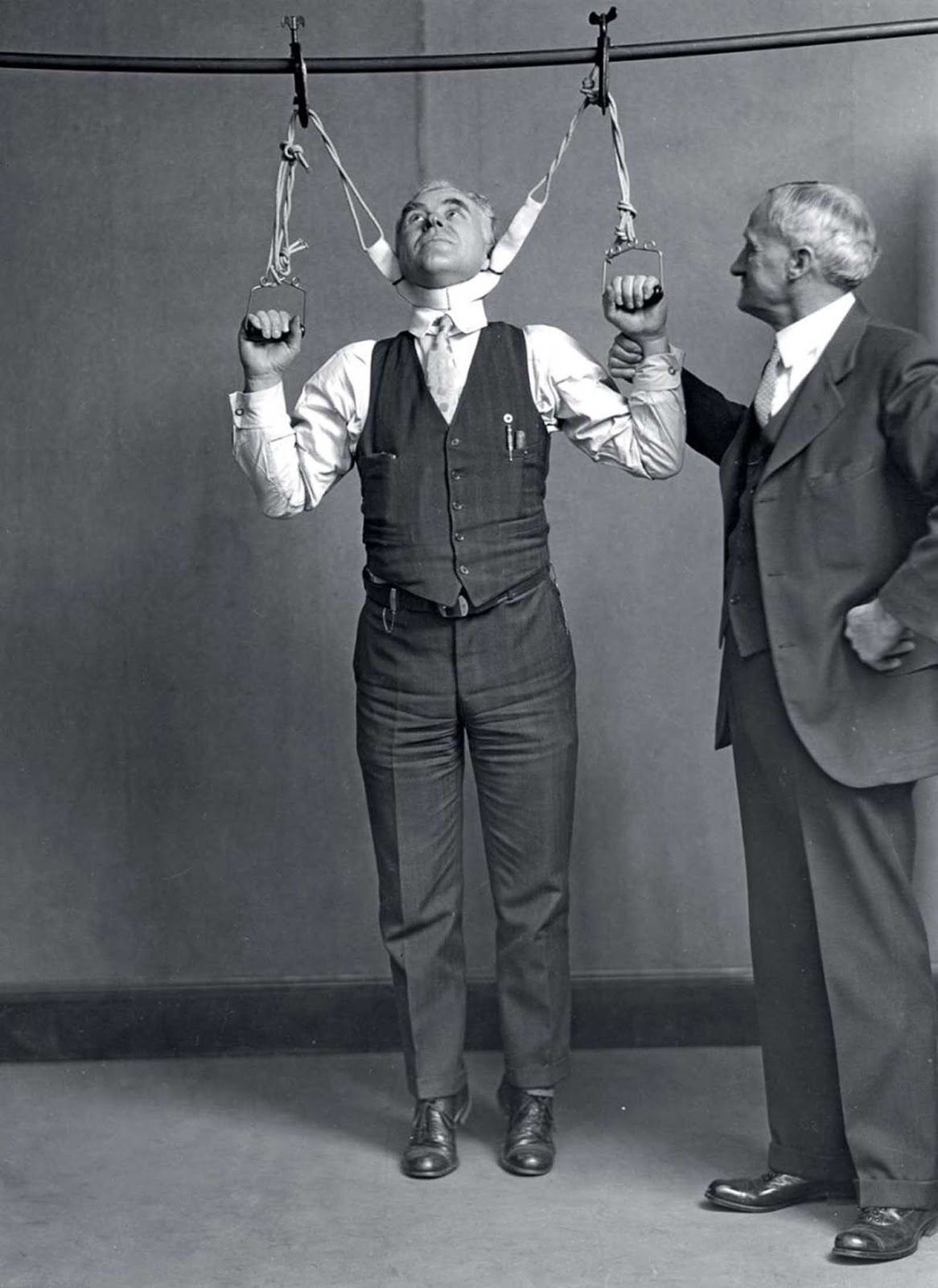 Post Office Department Inspector DF Angier (left) and Dr. LF Kebler, formerly of the Food and Drug Administration, try out a stretching device which claimed to increase height by 2 to 6 inches, 1931.