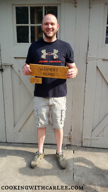 KC holding the winner's plaque with his name on it