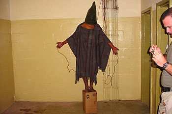 Arab prisoner in black hoodie with wires attached to his fingers forced to stand on a box