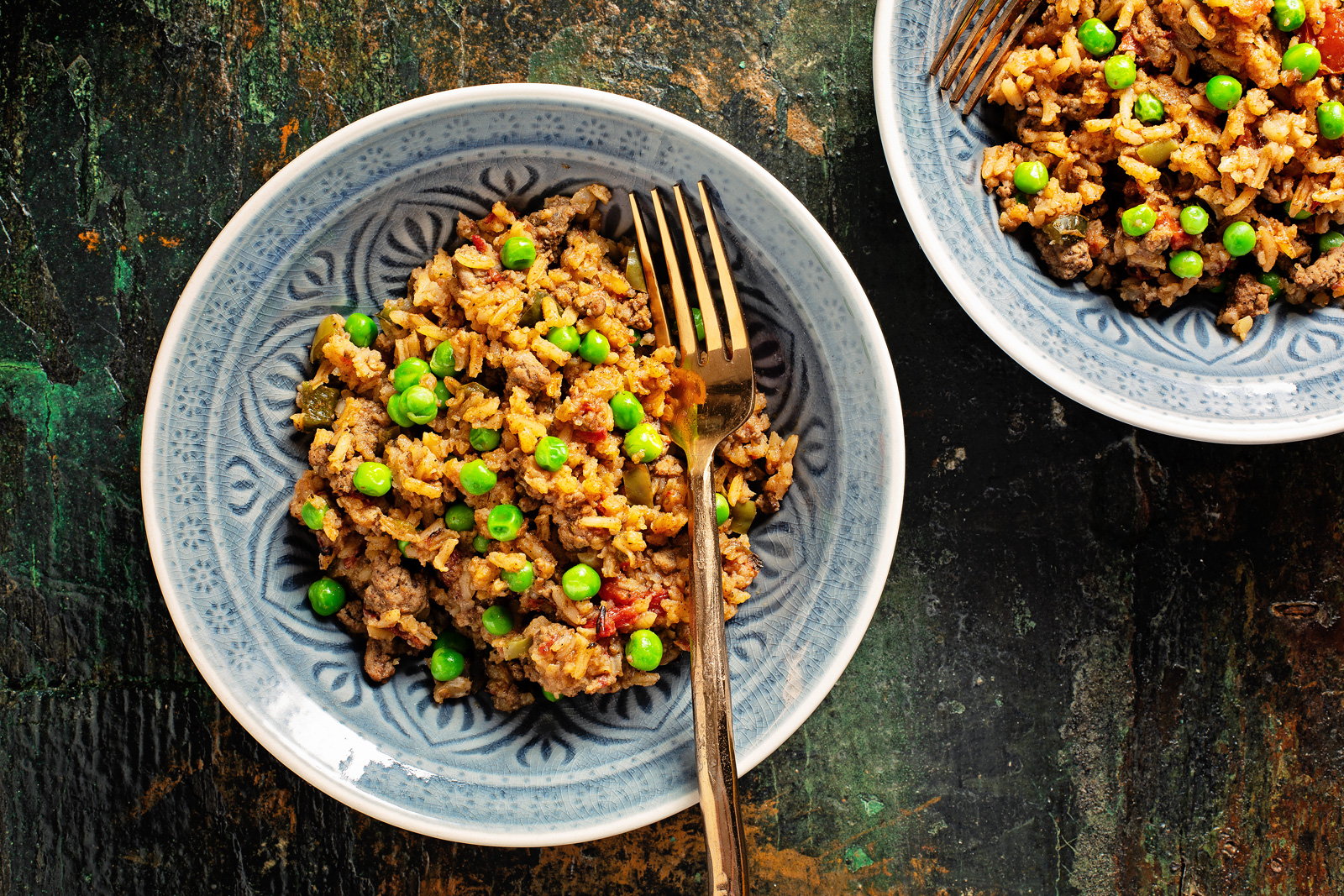 Bowls of Spanish rice with seasoned ground beef and peas.