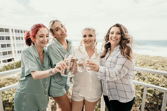 Bride with bridesmaids before getting ready on balcony