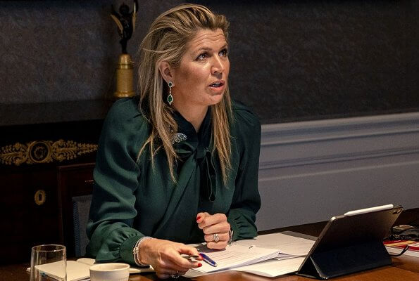 Queen Maxima wore an emerald green silk blouse by Gucci. emerald earrings