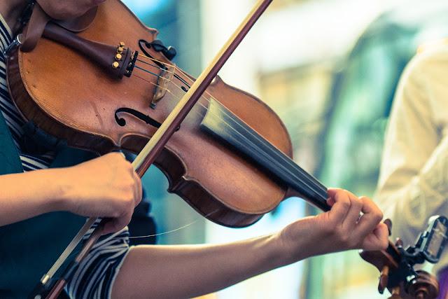 路上ライブしているバイオリン奏者のバイオリンの写真