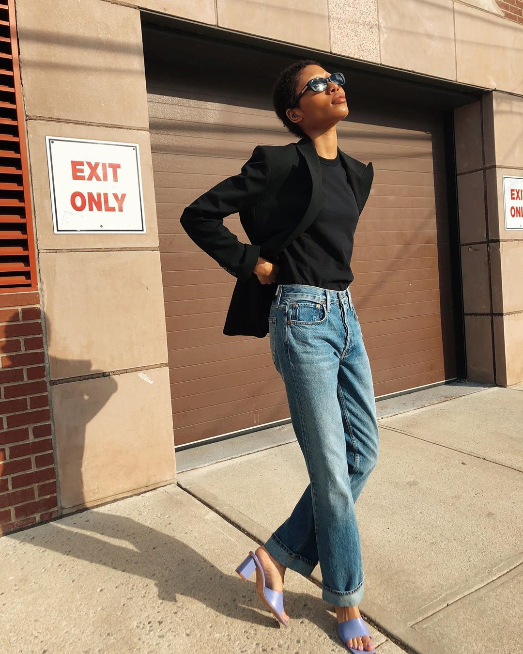 Minimalist Summer Outfit Idea: black squared sunglasses, a black blazer, a black t-shirt, long straight-leg jeans, and purple heeled mules