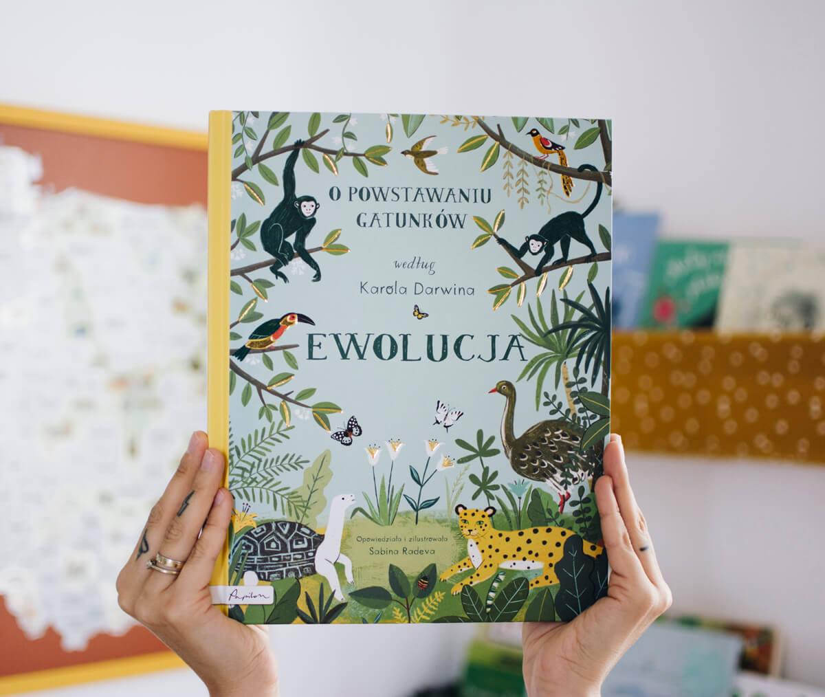 Dłonie trzymające książkę dziecięcą Ewolucja