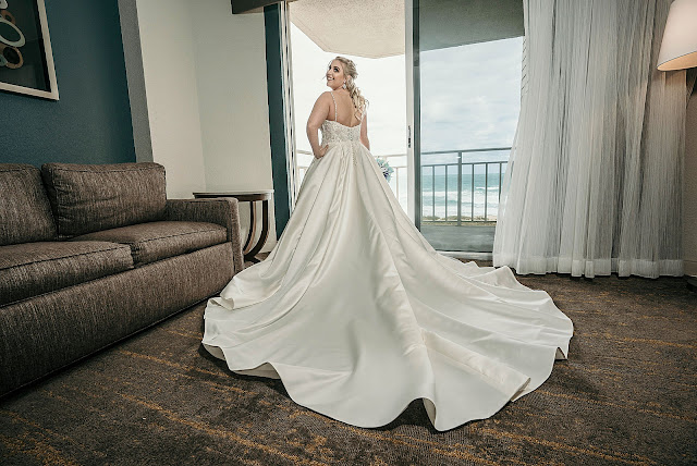 Bride with wedding dress on with stretched out train in hotel room