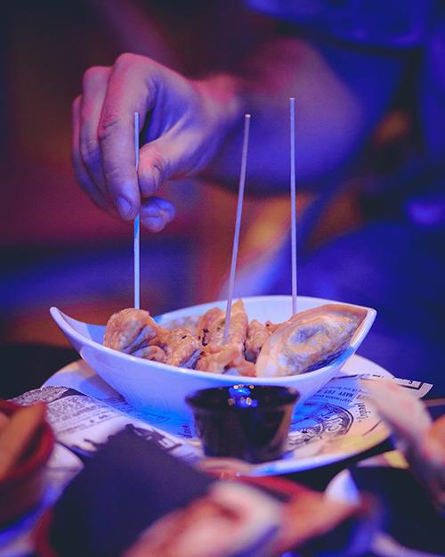 Una mano pincha una gyoza vegetal de un plato