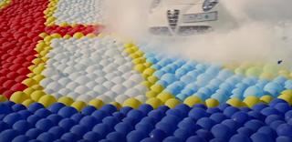 Werbung für eine Automarke indem ein PKW duch das Firmenlogo aus Luftballons fährt.