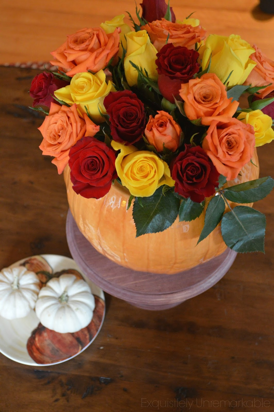 Pumpkin vase rose Floral Arrangement on cake stand with small pumpkins on a pumpkin dish nearby