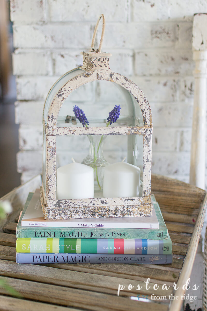 chippy metal candle lantern on top of books