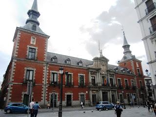 Edificio de tres plantas, de ladrillo visto y granito, con torres con chapitel en sus esquinas y portada de granito.