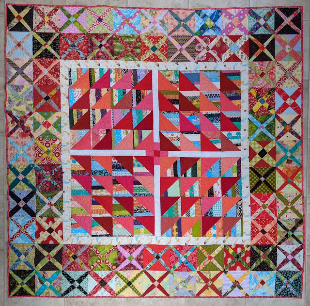 Medallion scrap quilt has The Square Deal block in the center surrounded by a narrow, white inner border and an outer border of two rows of lattice blocks in shades of red, pink, blue, and green