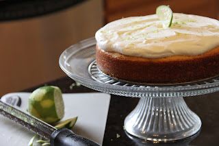 whole margarita cake on a cake stand with a lime next to it